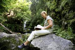 woman, mid 40, reading a book outdoors, ravennaschlucht gorge, hinterzarten,  - stock photo