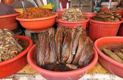 Dried fish and marinaded in a plastic bowl, fish market, vinh long, mekong de Stock Photos