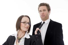 businesswoman holding businessman by his tie, emancipation in work - stock photo