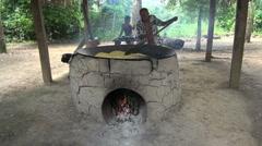 Amazon village cooking manioc on oven  Stock Footage