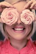 happy blond woman with two rosebuds - stock photo