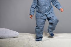 Playful little boy wearing blue pyjamas in bed Stock Photos