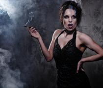 Beautiful vampire woman in black dress smoking Stock Photos