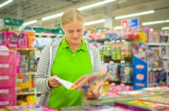 Young mother select kids books in supermarket Stock Photos