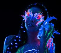 portrait of beautiful woman with body art glowing in ultraviolet light - stock photo