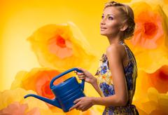 Beautiful dreaming woman in colourful dress with watering can among big yello Stock Photos