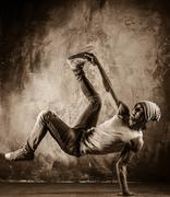 Toned picture of young man  doing acrobatic movements against grunge wall Stock Photos