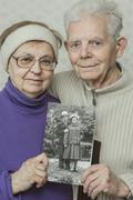 Portrait of senior couple holding up picture of themselves in their twenties Stock Photos