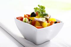 Greek salad with onions, tomatoes, capsicum, feta and olives in a small salad Stock Photos