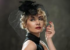 Elegant blond retro woman with red lipstick wearing little hat with veil Stock Photos