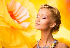 Beautiful young blond woman with closed eyes in colourful dress among big yel Stock Photos