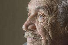Serious senior man looking away isolated over colored background Stock Photos