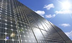 Photo-illustration of a large solar panel under blue sky brightly lit by the  Piirros