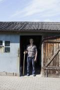 Portrait of confident mature man standing at the entrance of poultry farm Stock Photos