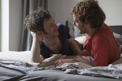 Affectionate gay couple looking at each while relaxing in bedroom Stock Photos