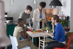 Friends preparing food in kitchen - stock photo