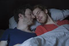 Relaxed young gay couple sleeping in bed Kuvituskuvat