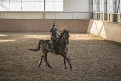 Woman riding horse in training stable Stock Photos