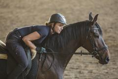 Side view of woman riding horse at ranch Stock Photos
