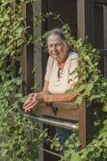 Portrait of senior woman with hands clasped at balcony Stock Photos