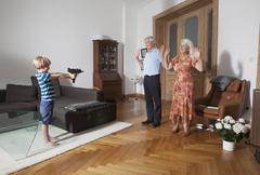 Little boy aiming with toy gun towards grandparents at home Stock Photos