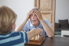 Shocked senior man with head in hands looking at grandson while playing chess at Stock Photos
