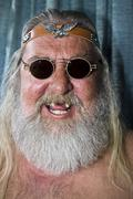 Stock Photo of laughing old rocker with missing front teeth, long hair and beard, sunglasses