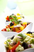 greek salad with onions, tomatoes, capsicum, feta and olives in small bowls - stock photo