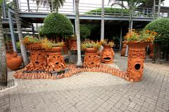 Trees with emotions with flower-beds in the Nong Nooch tropical botanic garden - stock photo