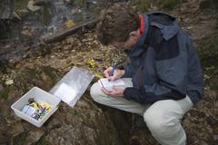 geocacher writing in a logbook, wutachschlucht gorge, black forest, germany,  - stock photo