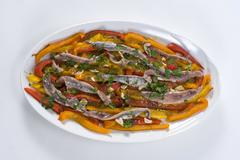 Anchovy fillets, roasted bell peppers in strips, with garlic, parsley, balsam Stock Photos