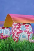 Easter egg painted as a house with corrugated cardboard as a roof Stock Photos