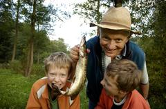Two boys, nine and eleven years old, proudly present the pike they caught wit Stock Photos