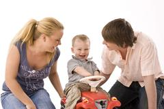 young couple playing with their 2-year-old son - stock photo