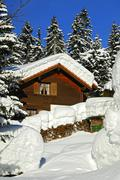Snow-covered block house on the edge of a forest, jura, switzerland Stock Photos