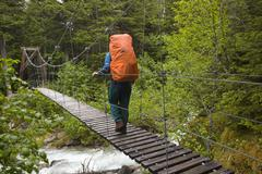 Female hiker with backpack crossing suspension bridge over taja river, near h Stock Photos