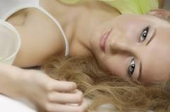 Portrait of a romantic young blond woman with daydreaming expression Stock Photos