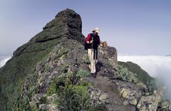 hiker at the descent from the roque de taborno rock formation, taborno, tener - stock photo