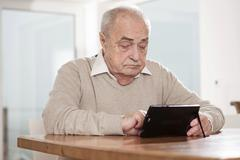 Elderly man using a netbook Stock Photos