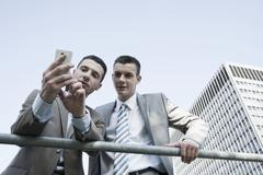 young businessman checking his mobile phone and showing something to a collea - stock photo