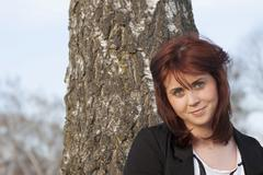 young woman, 25 years, portrait, standing in front of a tree trunk, germany,  - stock photo