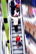 shopping abstract. people rush on escalator motion blurred - stock photo