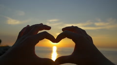 SLOW MOTION: Capturing the sun with heart shaped hands - stock footage