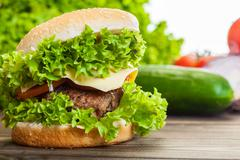 cheeseburger with lettuce, onions and tomato in a sesame bun on wooden table - stock photo