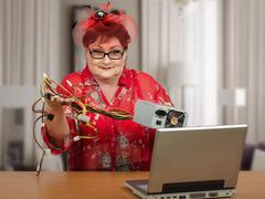mature housewife in red hat holding power supply - stock photo