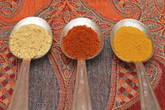spices on old spooks, curry, paprika and ginger powder - stock photo