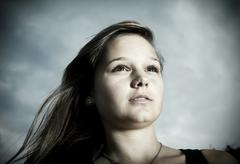 girl, 14 years in front of a cloudy sky, portrait - stock photo