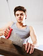 young man sawing a wooden beam - stock photo