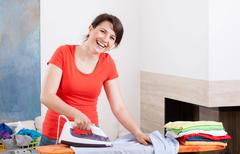 smiling woman ironing clothes - stock photo