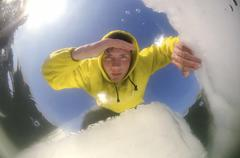 Man looking into an ice hole on the frozen black sea, a rare phenomenon which Stock Photos
